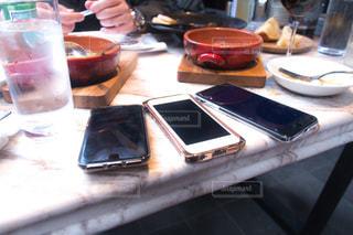 携帯電話がテーブルに座っている人々 のグループの写真・画像素材[855698]