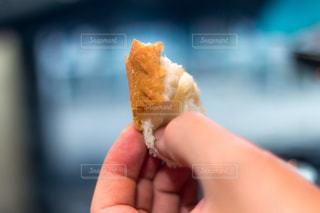 近くに食べ物のかけらを持っている手のアップの写真・画像素材[1079639]