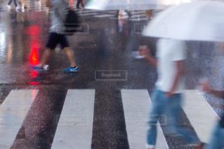 雨の日に傘を持って雨の中歩いている人の写真・画像素材[1086778]