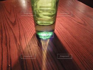 木製のテーブルの上に座ってガラス ボトルの写真・画像素材[1089277]