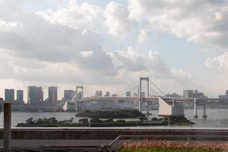 バック グラウンドで市と水の体の上の橋の写真・画像素材[1411154]
