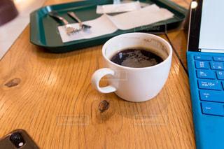 木製のテーブルの上に座ってコーヒー カップの写真・画像素材[1878618]