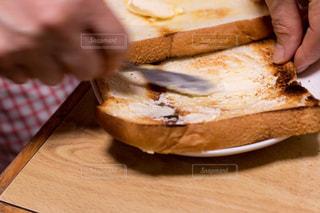 焦げたトーストにバターナイフでバターを塗るの写真・画像素材[1948916]