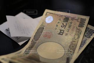 レシート、領収書と現金紙幣。千円札と一万円札。どうなる日本の今後、消費増税、キャシュレス化の波の写真・画像素材[2029125]
