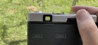 汚れたファインダー。フィルムカメラで写真撮影。カメラを持つ手と緑あふれる庭の写真・画像素材[3513446]