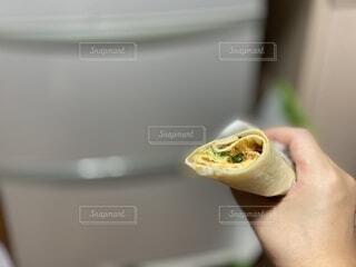 ピザのスライスを握る手の写真・画像素材[3705518]