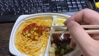 コンピューターのキーボードの前に食べ物がある容器の写真・画像素材[3727089]