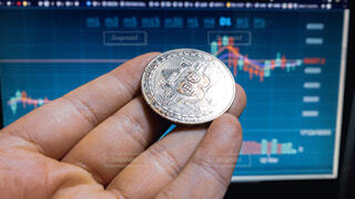 仮想通貨のチャート/値動き。シルバーの暗号資産(ビットコイン)を持つ手の写真・画像素材[4241075]