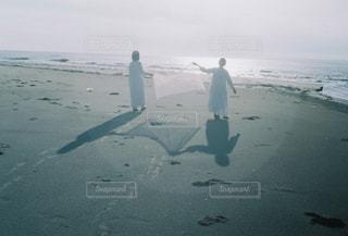 水域の隣の浜辺を歩いている男の写真・画像素材[2123453]