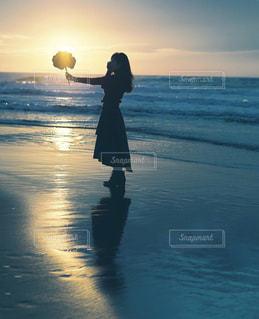 背景に夕日がある浜辺に立っている人の写真・画像素材[2123682]