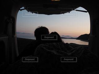 車の窓の外を見てベッドの上に座っている人の写真・画像素材[1018739]