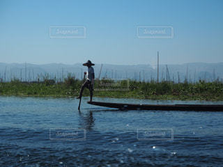 水の体の横に立っている人の写真・画像素材[971149]