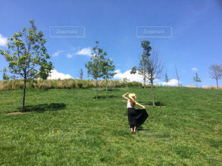 芝生のフィールドに立っている人の写真・画像素材[711008]