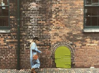 レンガ造りの建物の前に立っている人の写真・画像素材[2805170]