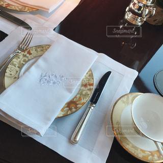 白プレート半分とテーブルの上に座ってのカットをトッピングの写真・画像素材[1000597]