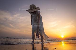 浜辺で、日没の前に立っている人の写真・画像素材[1594787]