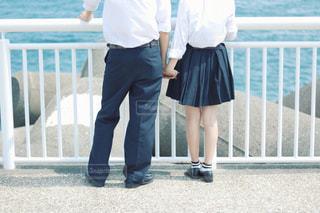 フェンスの横に立っている人の写真・画像素材[1369404]