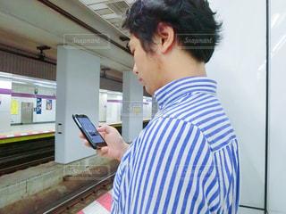 会社帰りの駅ホームでスマホ操作する男性の写真・画像素材[660001]