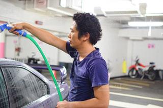 洗車場で車を洗う男性の写真・画像素材[666318]