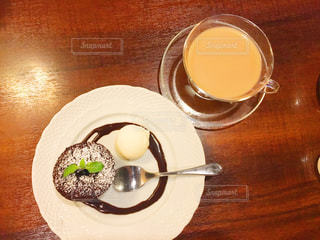 テーブルの上のコーヒー カップとプレートの写真・画像素材[728573]