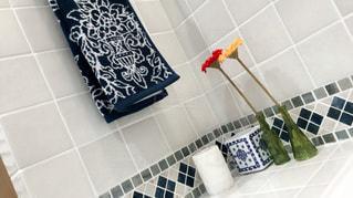 タイル張りの壁の隣に座っている白い浴槽付きのバスルームの写真・画像素材[729991]