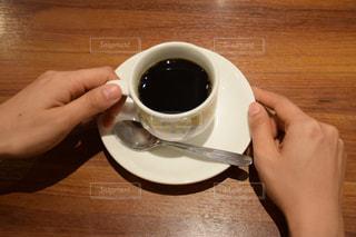テーブルの上のコーヒー カップを持つ手の写真・画像素材[732632]
