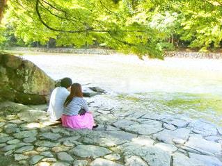 水の横にある岩の上に座っている女性 - No.750378