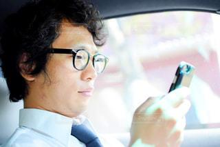 車内でスマホを操作する男のアップの写真・画像素材[757705]