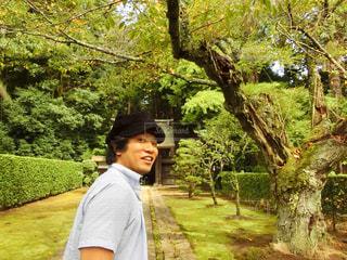木の隣に立っている男の写真・画像素材[758877]