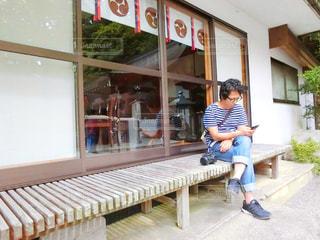 建物の前にあるベンチに座っている男の写真・画像素材[761892]