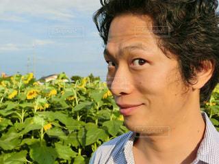 カメラにポーズする花の前にいる男性の写真・画像素材[761938]