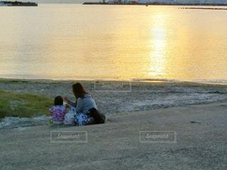 水の体の近くのビーチに座っている男 - No.785571