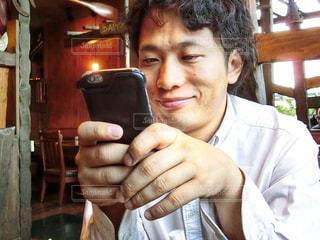 携帯電話で話している椅子に座る男性の写真・画像素材[785586]