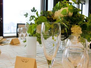 グラスのワインやテーブルの上に花の花瓶の写真・画像素材[935653]