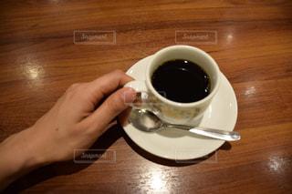 木製のテーブルの上に座ってコーヒー カップの写真・画像素材[936352]