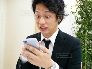 スーツと携帯電話を身に着けている男の写真・画像素材[972102]