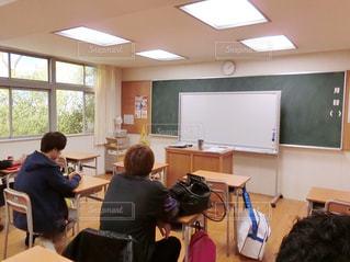 部屋で机に座っている人々 のグループの写真・画像素材[981410]