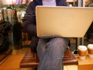 ラップトップを使用してテーブルに座っている人の写真・画像素材[993353]