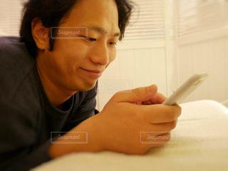 ベッドの上でスマホをいじる男性の写真・画像素材[994363]