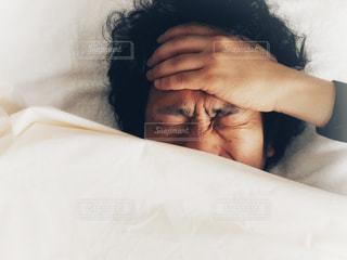 寝込んでいる男性の写真・画像素材[998231]