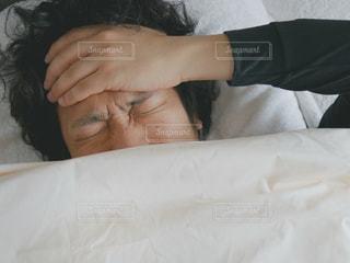 ベッドの上で起きた男性の写真・画像素材[998377]