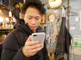 携帯電話を持っている人の写真・画像素材[1002410]