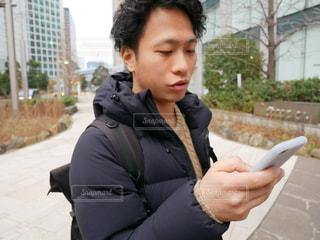 建物の前に立っているスマホ操作する男性の写真・画像素材[1002416]