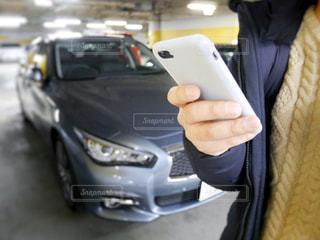 事故車の前でレッカー車に電話する男性の写真・画像素材[1002441]
