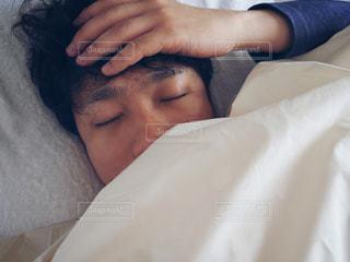 ベッドの上で横になっている人の写真・画像素材[1003344]