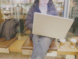 ラップトップを使用してテーブルに座っている人 - No.1013031