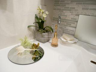 テーブルの上の花の花瓶をのせた白プレートの写真・画像素材[1033484]