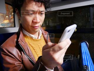 バス車内でスマホを持って困ってる男性の写真・画像素材[1039036]