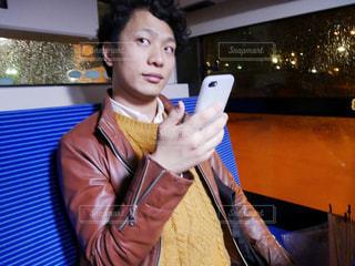 バス車内で、スマホをいじりながら考え事をする男性の写真・画像素材[1039040]