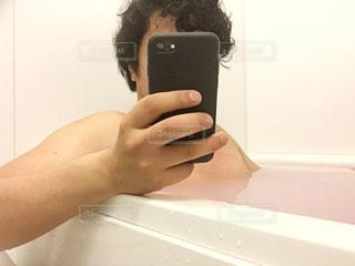 お風呂で男性が携帯電話を使用している。の写真・画像素材[1128884]